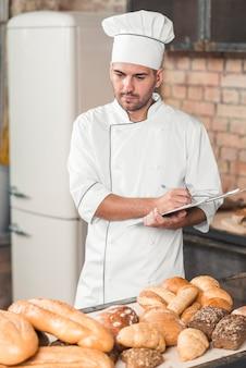 Baker en uniforme prenant des notes de pain cuit assorti