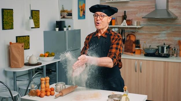 Baker vêtu d'un uniforme vomit de la farine debout près de la table. cuisinier professionnel avec claps bonete et mouche en poudre, chef à la retraite saupoudrant d'ingrédients rew sur la pâte préparant du pain traditionnel