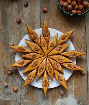 Baklava de biscuits de vacances traditionnelles de l'azerbaïdjan sur une plaque blanche sur le rustique avec des noix