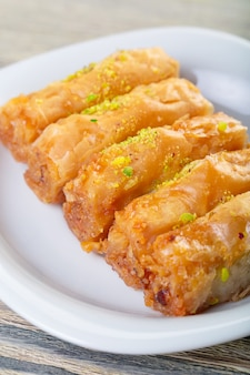 Baklava dessert arabe traditionnel avec noix de cajou, noix et cardamome avec une branche d'eucalyptus sur une table en bois