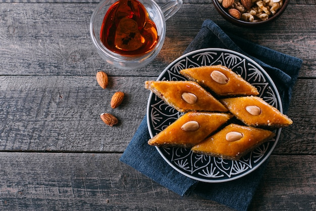 Baklava. dessert du ramadan. dessert arabe aux noix et au miel, tasse de thé sur un fond en bois.
