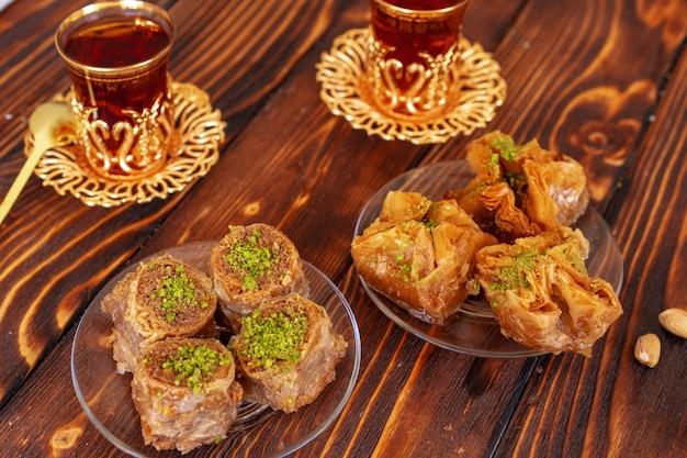 Baklava doux turc avec du thé turc sur fond de bois