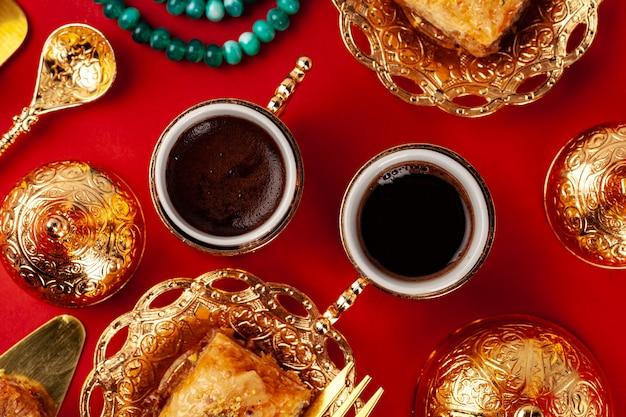 Baklava turc et café dans la vaisselle orientale sur fond rouge