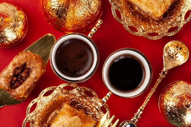 Baklava turc et café dans la vaisselle orientale sur tableau rouge