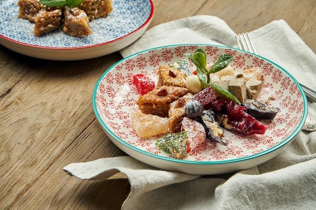 Baklava turc classique avec pistaches et miel dans une plaque en céramique sur une surface en bois. pâtisseries et bonbons turcs. fermer
