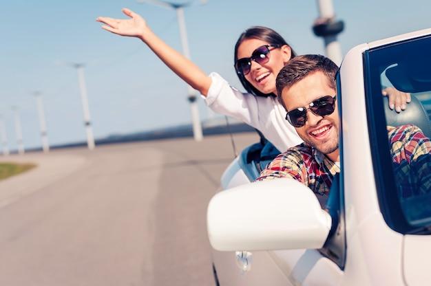 Balade amusante. heureux jeune couple profitant d'un voyage sur la route dans leur cabriolet blanc
