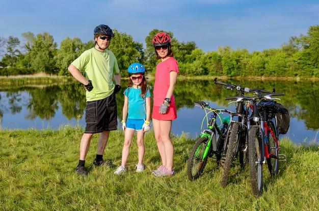 Balade à vélo en famille à l'extérieur, parents actifs et enfants à vélo et se détendre près de la belle rivière