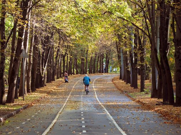 Balade à vélo le long de la magnifique allée d'automne du parc sokolniki. moscou.