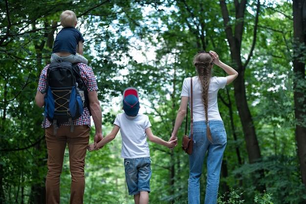 Balades en famille dans la nature. maman, papa et deux fils. famille soudée. vue arrière