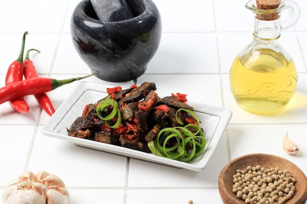 Balado paru, nourriture traditionnelle indonésienne à base de poumons de boeuf. cuit avec beaucoup de piment, d'ail, d'échalotes et de feuilles de citron vert. délicieux avec un goût épicé.