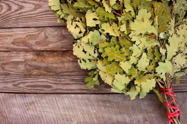 Balai en chêne pour un bain sur fond en bois.
