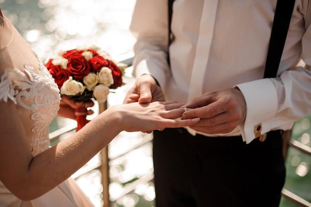 Balai mettant sur une bague de mariage en or à un doigt de mariée tendre dans le fond de la mer