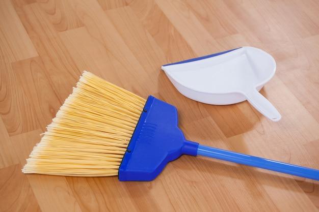 Balai et pelle à poussière sur plancher en bois