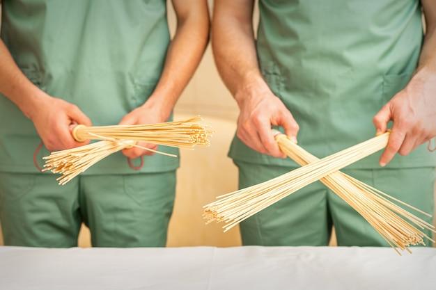 Balais de massage en bambou dans les mains
