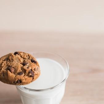 Balance à biscuits aux pépites de chocolat sur le bord du verre avec du lait