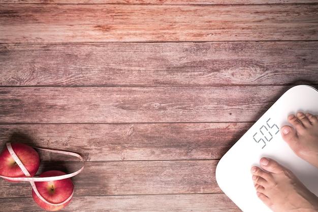 Balance digitale et pieds de femmes debout sur une balance et une pomme rouge diète