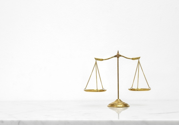 Balance d'écailles d'or mis sur le comptoir de table en marbre blanc avec espace libre