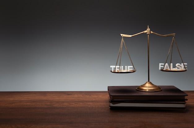 Balance en laiton doré placée sur un cahier, un bureau en bois et un fond gris avec du texte en bois true false