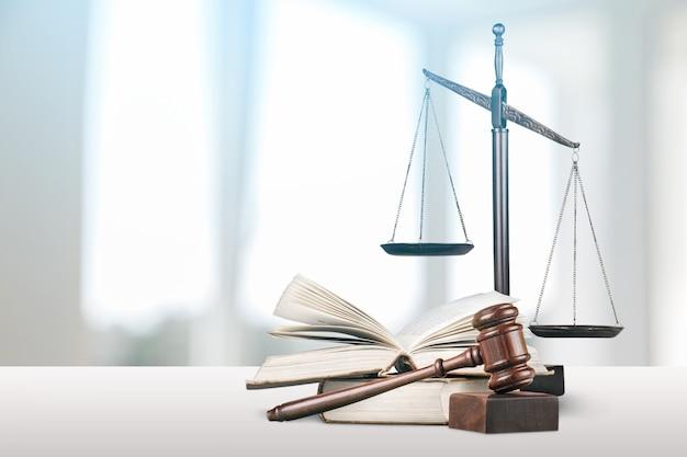 Balances et livres de justice et marteau en bois sur table. notion de justice
