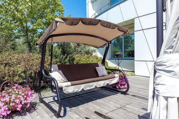 Balançoire auvent de jardin banc sur patio pavé de bois dans le jardin du domaine en été