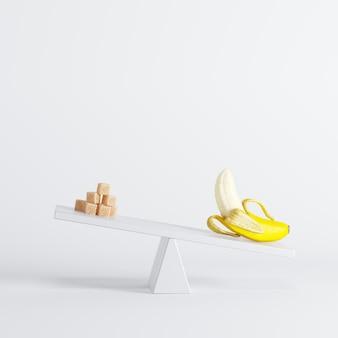 Balançoire à banane basculant avec des sucres à l'extrémité opposée sur fond blanc. idée de nourriture minimale.