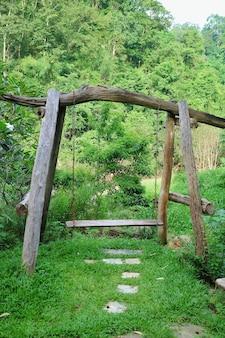 Une balançoire en bois dans le jardin avec fond de montagne verte.
