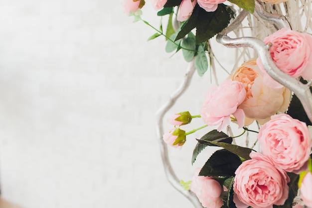 La balançoire en bois ornée de fleurs artificielles.