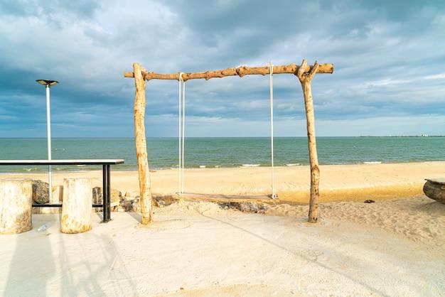 Balançoire en bois sur la plage avec fond de plage de mer