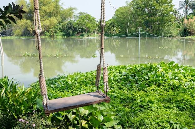 La balançoire en bois solitaire près de la petite rivière avec la lumière du soleil en été, située dans le restaurant local dans la zone de détente pour la famille, vue de face avec l'espace de copie.