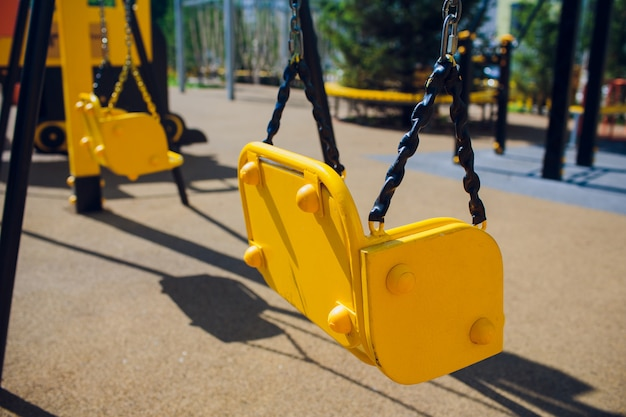 Balançoire à chaîne vide se balance dans l'aire de jeux pour enfants.