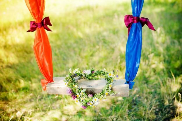 Sur une balançoire, une couronne de fleurs. cœur