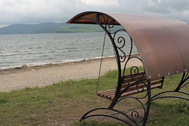 Balançoire forgée avec un toit au bord de la mer.