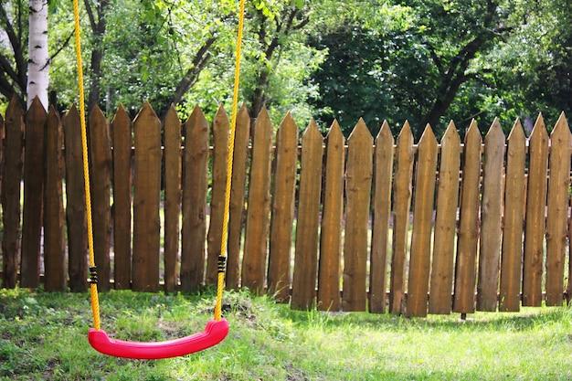 Balançoire en plastique rouge pour enfants vides sur des cordes jaunes.