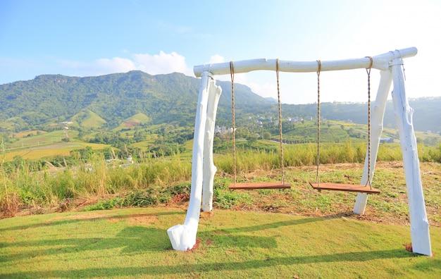 Balançoire vide sur la colline avec le lever du soleil du matin.