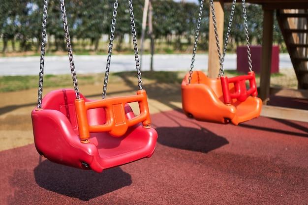Balançoires sur l'aire de jeux dans le parc pour enfants
