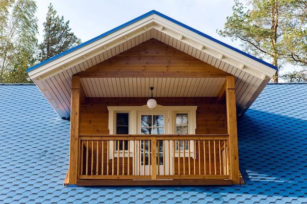 Balcon en bois dans une petite maison avec un toit bleu journée d'automne en polycarbonate