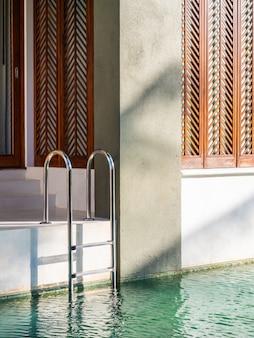 Balcon extérieur au bord de la piscine avec escalier et chaise