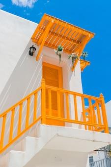 Balcon jaune et porte et mur blanc