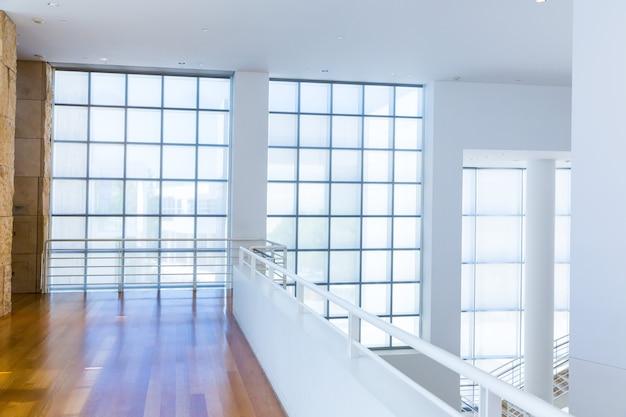 Balcon avec plancher en bois contre le mur de blocs de verre