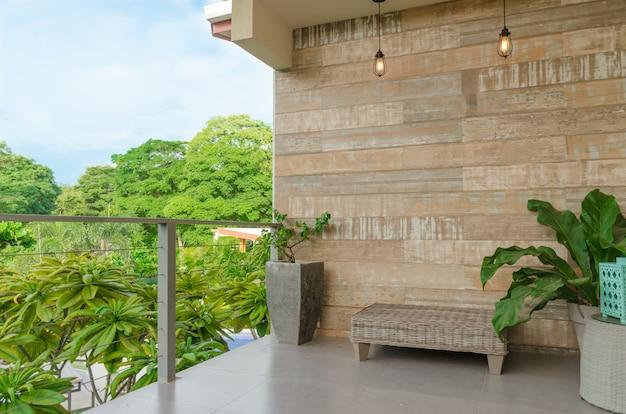 Balcon avec vue verte et ciel bleu clair, lampes, plantes et banque.