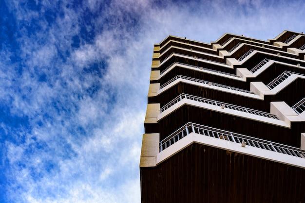 Balcons d'immeuble d'habitation avec fond de nuages bleus, fond avec espace de copie.