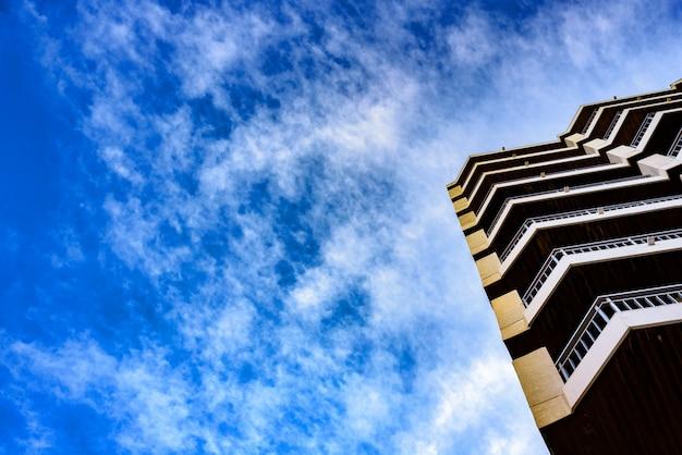 Balcons d'immeuble d'habitation avec fond de nuages bleus,