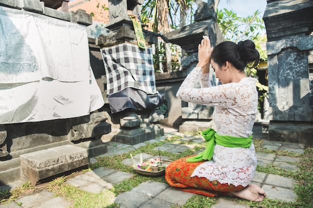 Balinais femme priant temple sur les petits sanctuaires dans les maisons