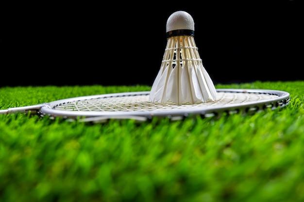 Balle de badminton et raquette sur l'herbe sur fond noir