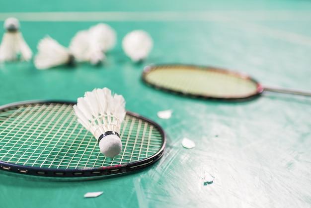 Balle de badminton (volant) et raquette sur le sol de la cour