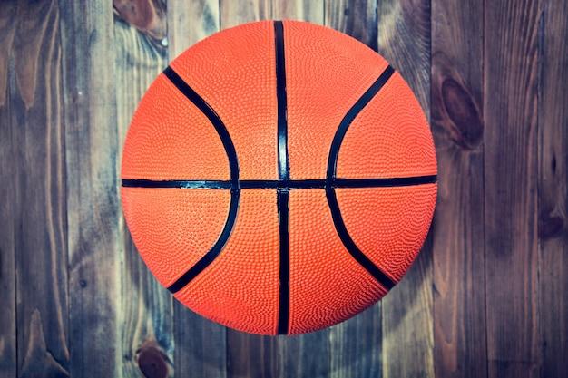Balle de basketball sur parquet en bois.