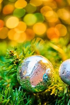 La balle dans les branches vertes des lumières brûlantes bokeh.