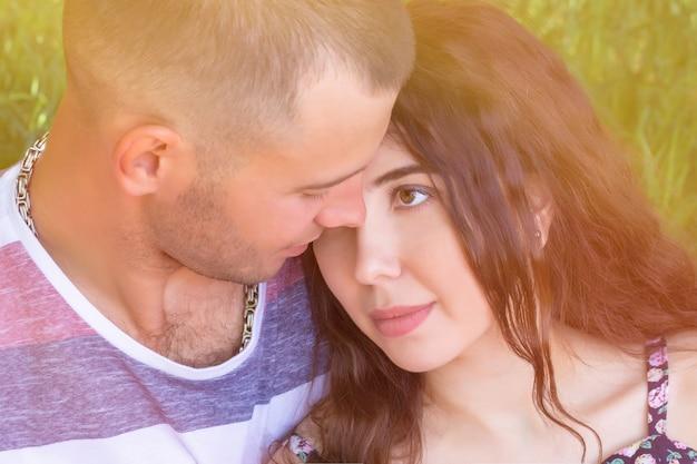 Balle dans la tête d'un jeune couple amoureux affectueux. bouchent le portrait d'une jolie fille brune et mec aux yeux fermés