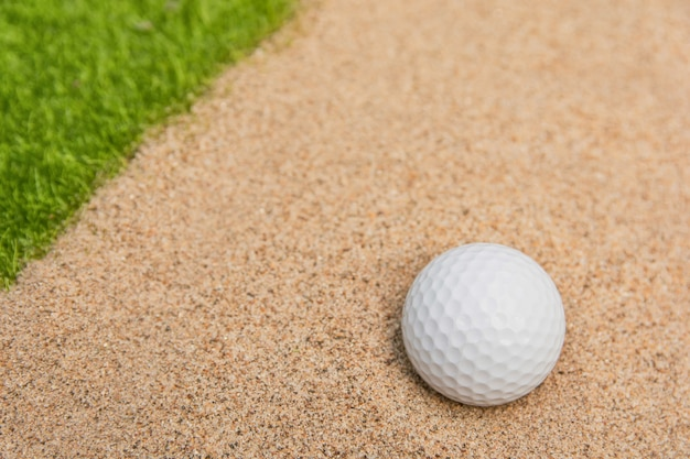 Balle de golf blanche dans le bunker de sable sur le terrain de golf