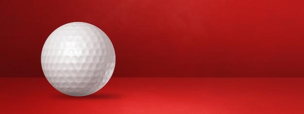 Balle de golf blanche isolée sur une bannière de studio rouge.